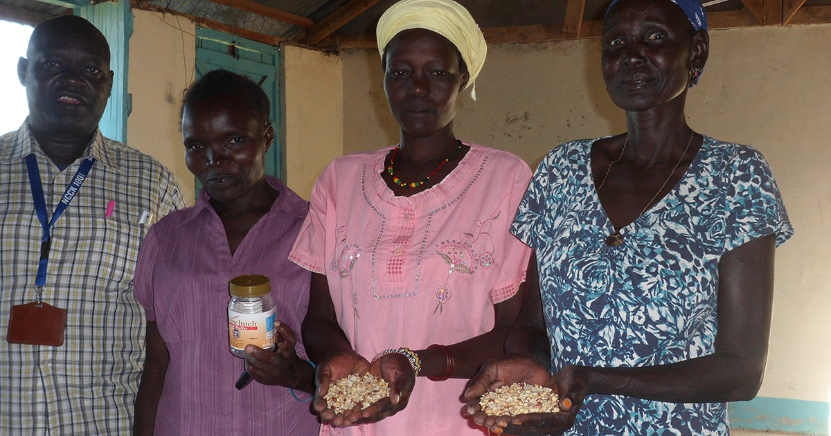 Ana Daborah (right) and other refugees, along with a staff member from the National Council of Churches of Kenya—which helps fund the peanut butter project with PWRDF—show some of the supplies for their peanut butter business in the Kakuma refugee camp.  Submitted photo by Jeannethe Lara