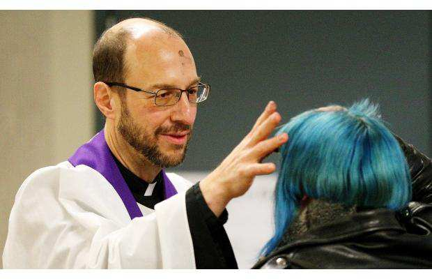 Pappas applies ashes to an Edmonton commuter as part of the diocesan Ashes to Go program, which offers ashes and blessings to city residents on Ash Wednesday. Photo by Margaret Marschall