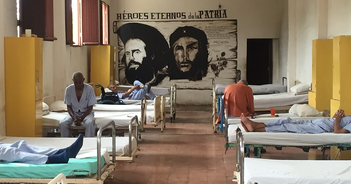 A painting depicting Cuban revolutionaries Camilo Cienfuegos and Che Guevara overlooks one of two dormitories at the Colony shelter for poor elderly men in Havana, Cuba.
