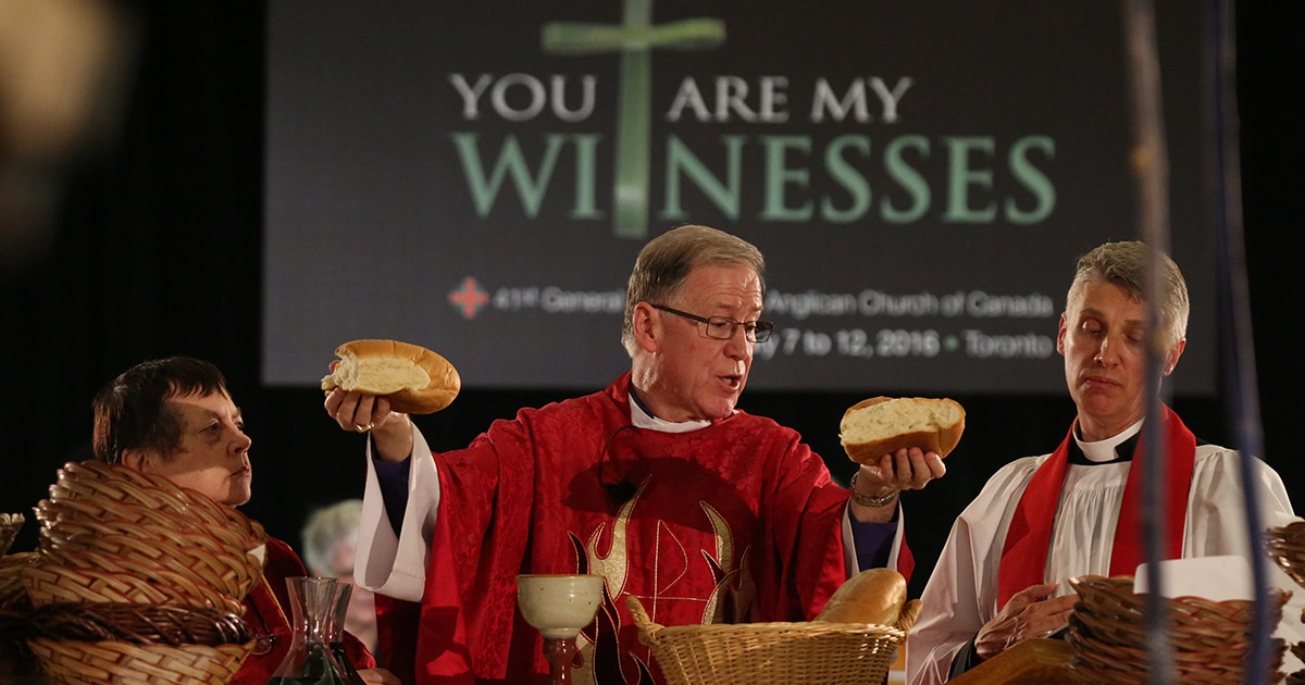 Archbishop Fred Hiltz, Primate, breaks bread during the opening Eucharist at the 41st General Synod of the Anglican Church of Canada. Photo by Art Babych