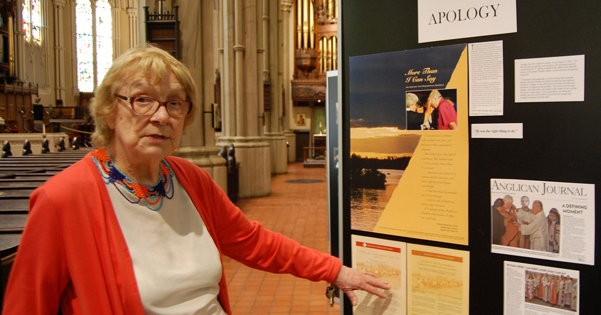Archivist Nancy Mallett points to a copy of the official apology given by then-Primate Michael Peers on behalf of the Anglican Church of Canada for its role in the Indian residential school system—one of the items on display over the summer at St. James Cathedral in Toronto. Photo by Matt Gardner