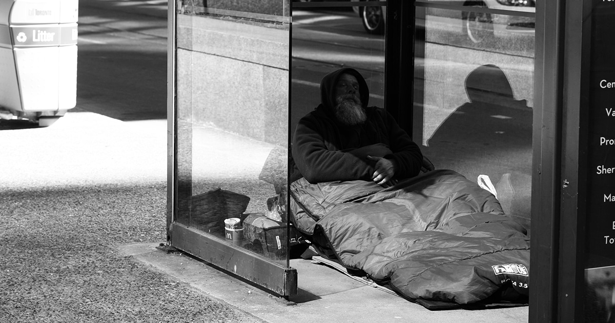 A homeless man seeks refuge inside a bus shelter at York and Wellington Streets in downtown Toronto, Ont.. Photo by Danielle Scott, via Wikimedia Commons