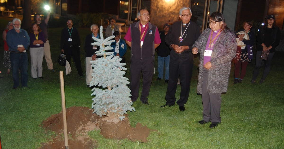 Bishop Lydia Mamakwa (foreground, right) speaks before the planting of a symbolic evergreen tree at the end of the 2015 Sacred Circle, as Diocesan Bishop of Missinipi Adam Halkett (foreground, left) and Anglican Council of Indigenous Peoples co-chair Sid Black (foreground, centre) listen.