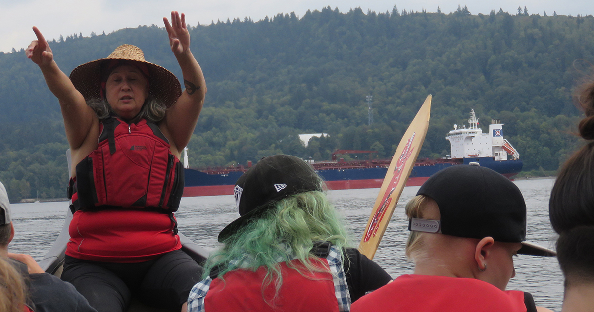 With the Tsleil-Waututh First Nation, participants at the first Sacred Earth Camp paddle a traditional canoe on the Salish Sea opposite an oil tanker. Submitted photo by Laurel Dykstra