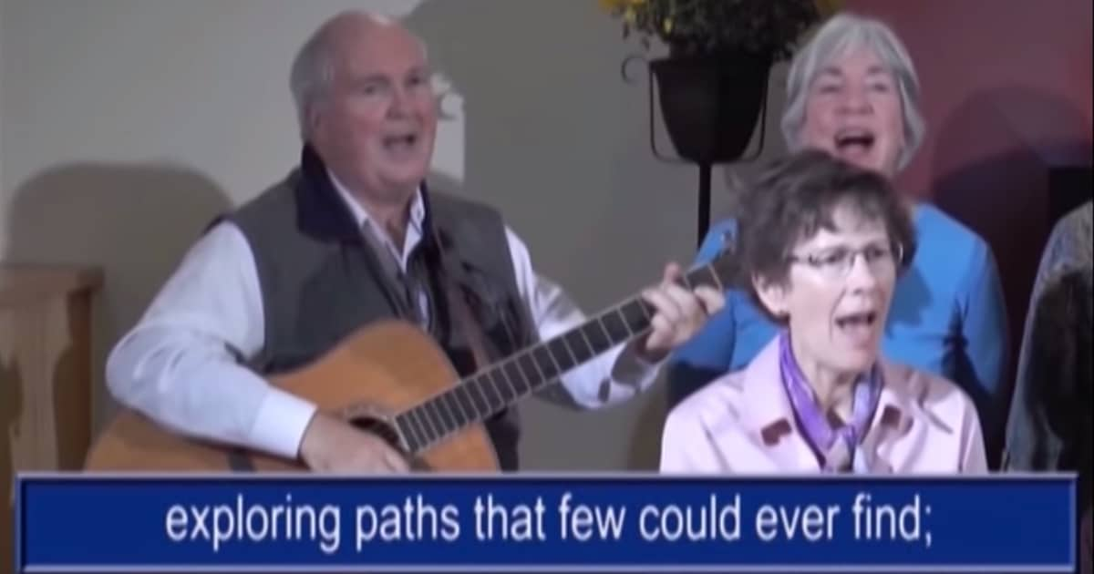 Bishop Gordon Light, retired bishop of the Anglican Parishes of the Central Interior, plays guitar and sings along with members of the Khoros vocal group as lyrics from the song are displayed at the bottom in a screenshot from the 'Sing Hallelujah!' video hymnal.