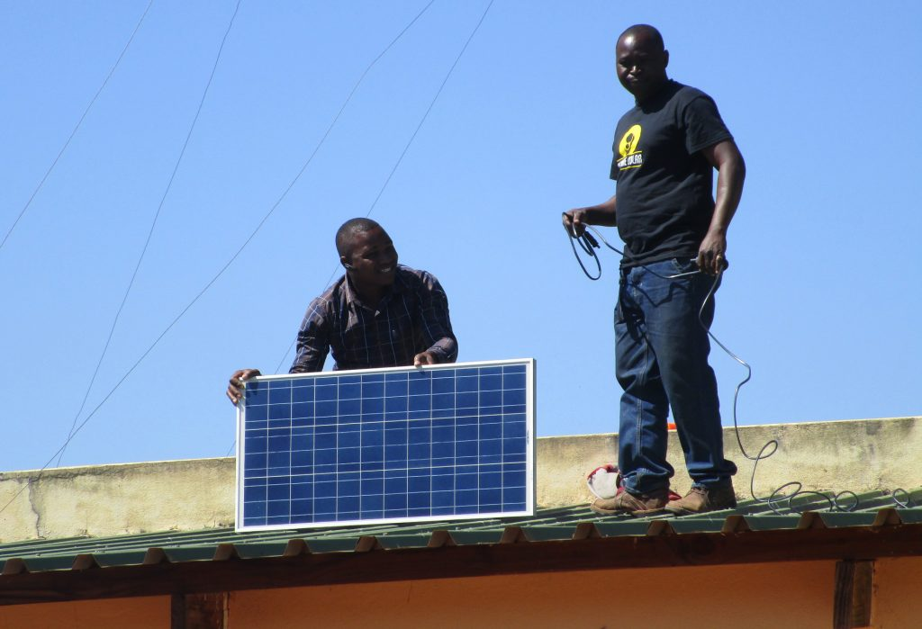 Installation of solar panels on the roof of of a health clinic to power solar suitcase. Submitted photo by PWRDF