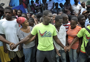 Men hold back a crowd at a food distribution in the Santa Teresa camp in Petionville, Haiti. Hundreds of families left homeless by the Jan. 12 earthquake live here. The ACT Alliance provides a variety of services in this camp. PHOTO BY PAUL JEFFREY/ACT ALLIANCE