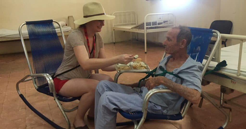Justice Camp participant Alicia Archbell helps feed a resident at the Colony shelter.