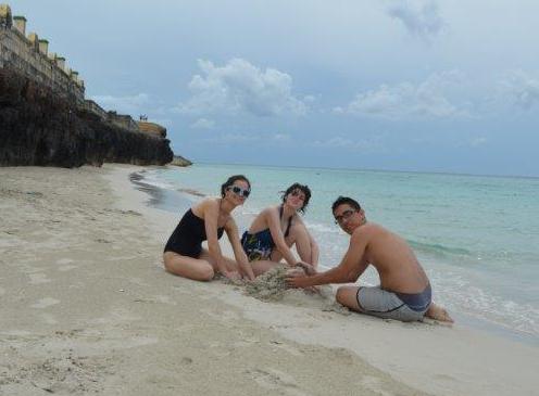 Left to right: Justice Camp participants Katelyn James, Sierra Robertson-Roper, and Jorge González Nuñez build a sand castle at a beach near Varadero.