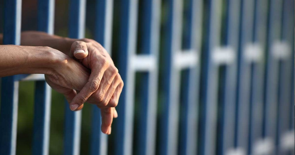 Hands in a jailcell. Photo: Shutterstock.
